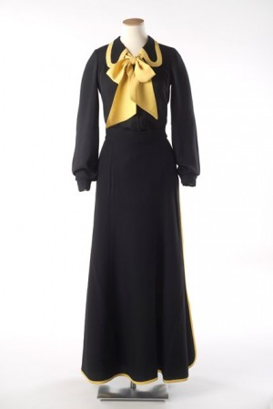 It is made from synthetic black crêpe and the long A-line skirt features  two side splits. These and the hem are bound with yellow braid. 7fb5d72f52df